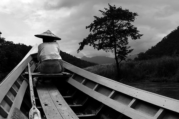 A woman takes a boat ride to a Paduang village in Northern Thailand. thumbnail