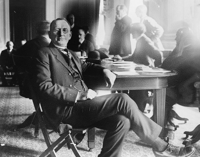 Black and white image of man in glasses seated at wood table