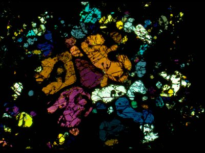 A polarized-light microscopy image (in background) of a section from the Allende meteorite is one-thousandth of a millimeter thin.