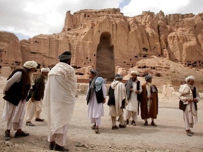 Afghan men stand near the ruins of the ancient Buddhas of Bamiyan.