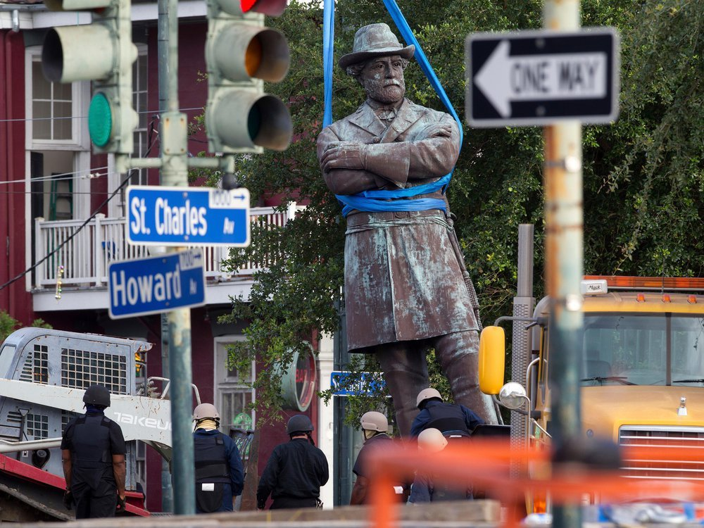 A statue of Confederate General Robert E. Lee is lowered to a truck for removal Friday, May 19, 2017, from Lee Circle in New Orleans.