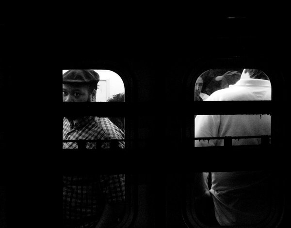 Man staring into the lens through a subway window. thumbnail