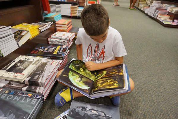 A boy reading a book in a library Honolulu thumbnail