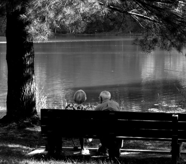 Couple in black and white sitting on a bench in front of the lake  thumbnail