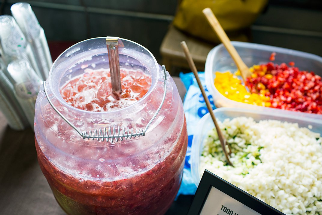 A container of fresh, red agua fresca is mixed on a table.