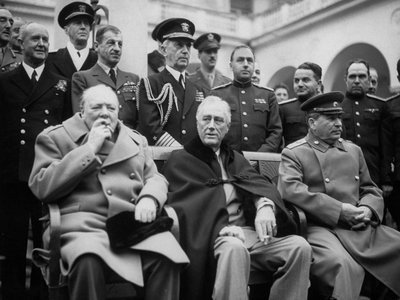 Fleet Adm. William D. Leahy stands directly behind President Franklin D. Roosevelt, who is seated between Winston Churchill (left) and Joseph Stalin (right), at the Yalta Conference during World War II.