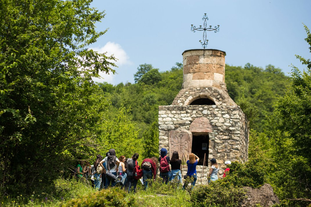 Nestled in a forest stands a small, stone chapel. It is surrounded by tourists taking photos.