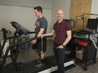 Steven Devor, front, developed the automated treadmill using off-the-shelf parts, including an inexpensive sonar range finder and an existing treadmill. (Photo by Jo McCulty, Courtesy of Ohio State University)