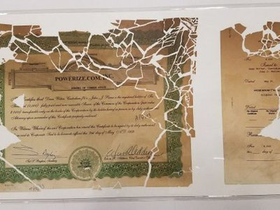The stock certificate pieced back together and encased in mylar