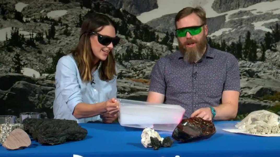 Two people sitting at a table with rock samples on it.
