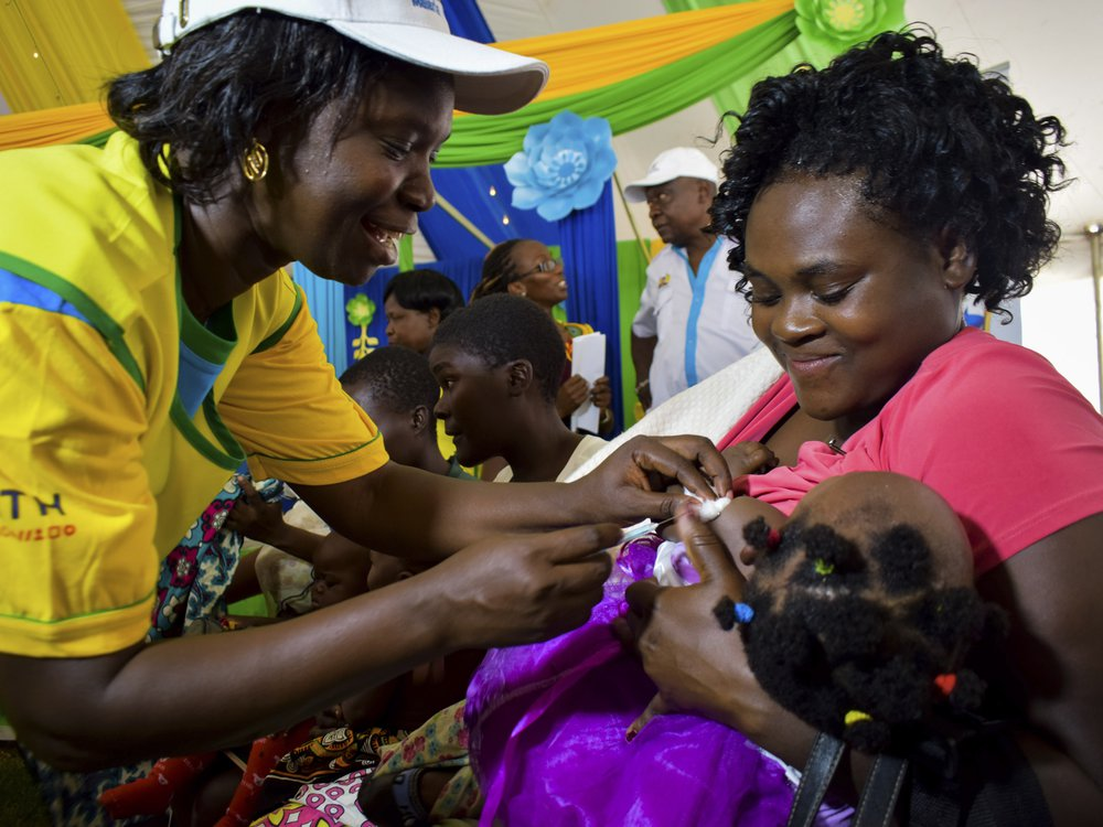 A health worker vaccinating a child against malaria in Kenya. The child is being held by her mother who is smiling.