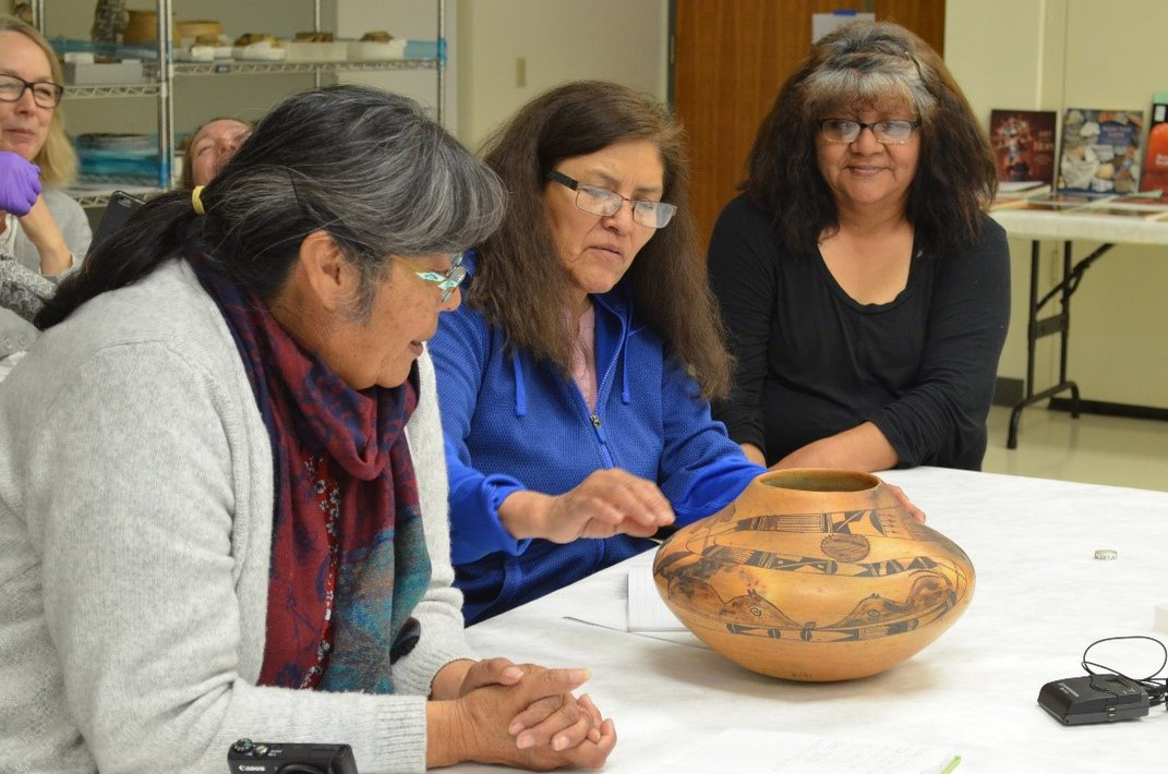 People sitting at a table with indigenous pottery.
