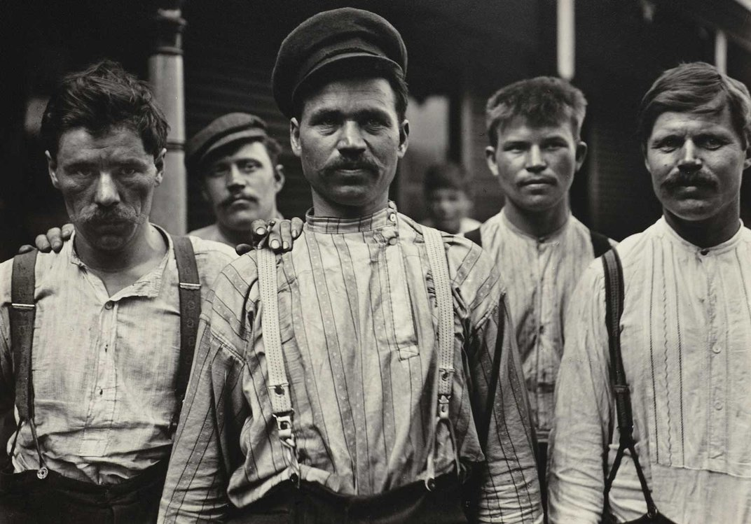 Black and white photo of five men, all with mustaches and suspenders, and some with hats