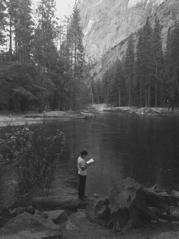 Boy reading Merced river, Yosemite thumbnail