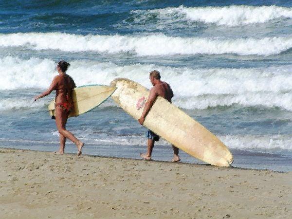 A couple walks along Virgina Beach looking for a wave to ride. thumbnail