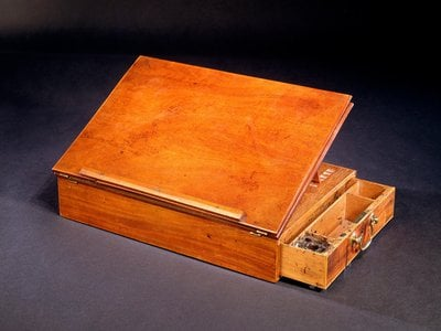 When the writing box is unfolded, it offers a slanted writing surface, a drawer to hold inkwells and quills, and plenty of room for paper.