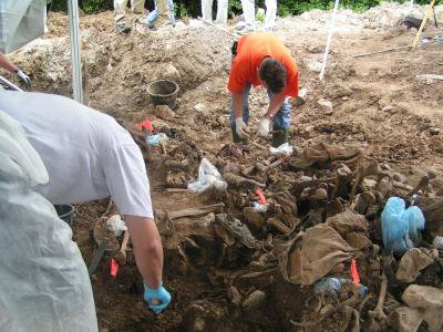 Workers examine remains at a mass grave in eastern Bosnia in 2004.