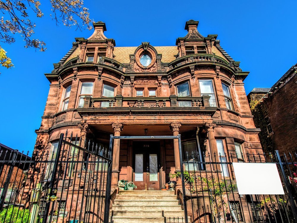 A front view of an ornate brownstone mansion, with columns, a circular window in the center, turret-like shapes on either side and a peaked roof