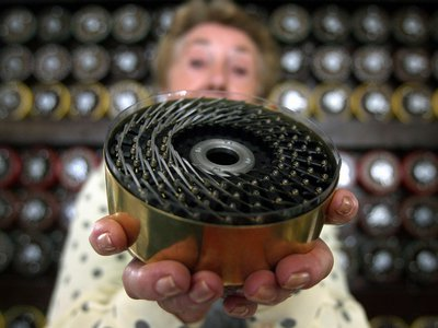 A former bombe operator shows the back of a drum from the decryption machine at Bletchley Park.