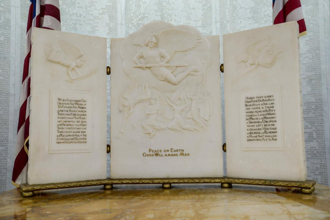 Three panel carving of angels with text