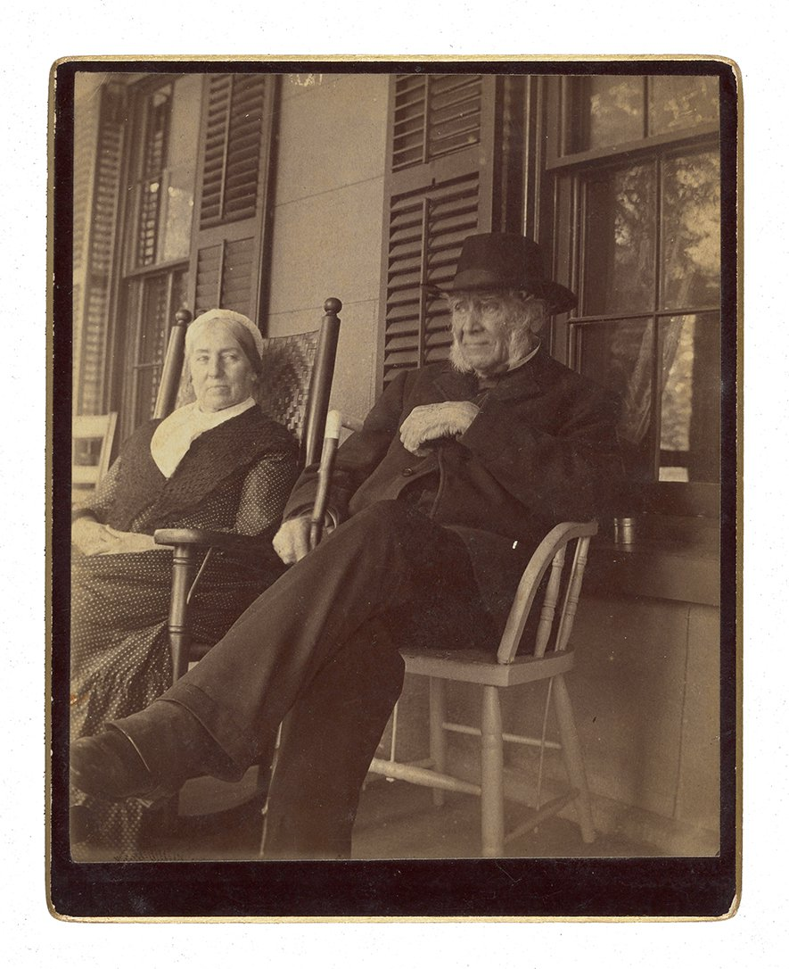 An older couple sitting on a porch. The man sits in a chair  in a suit and hat, holding a cane with his legs crossed. The woman has a bonnet on and sits in a rocking chair.