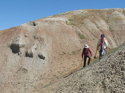 Allie and Elizabeth make their way across a steep badland slope as we prospect for new sites to collect Paleocene-Eocene Thermal Maximum plant fossils. The red layers on the hill behind them represent the lowest part of the PETM.