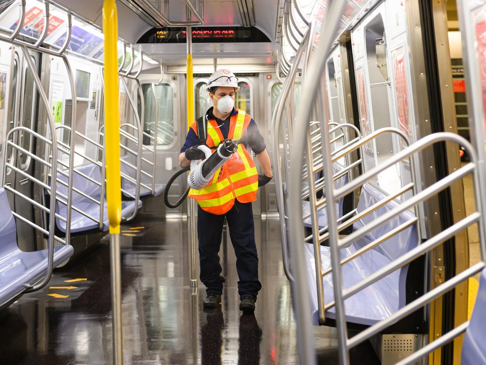 MTA worker wearing hard hat, mask, and safety vest uses a bulk disinfectant machine to deep clean an MTA subway car