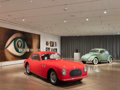 """An installation view of """"Automania"""" at the Museum of Modern Art in Manhattan. The red car in front is a Cisitalia 202 GT Car (1946) designed by Italian firm Pininfarina; the green car in the background is a German """"Beetle,"""" a.k.a. a Volkswagen Type 1 Sedan (1949).  The lithograph on the wall is Watch the Fords Go By (1937) by A. M. Cassandre."""