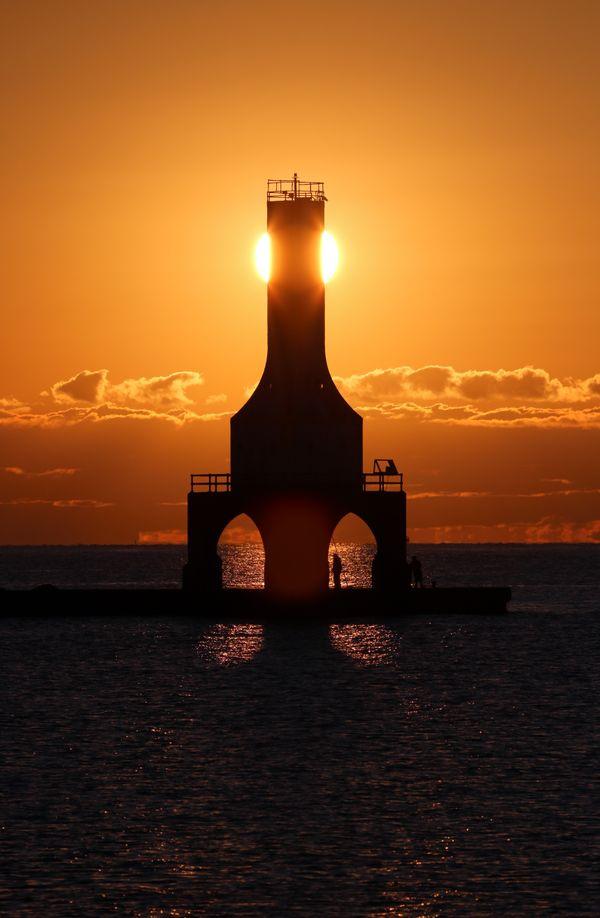 Sunrise behind the Port Washington,Wisconsin lighthouse over Lake Michigan thumbnail
