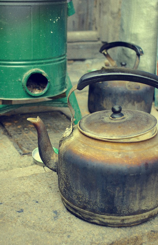 Water jugs on the ground beside an old style coal stove thumbnail