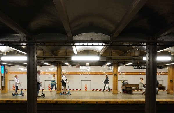 A family riding scooters on subway platform.  thumbnail