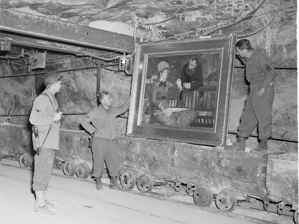 Three men in army gear stand in a bunker, holding a large painting of a man and a woman in an elegant frame