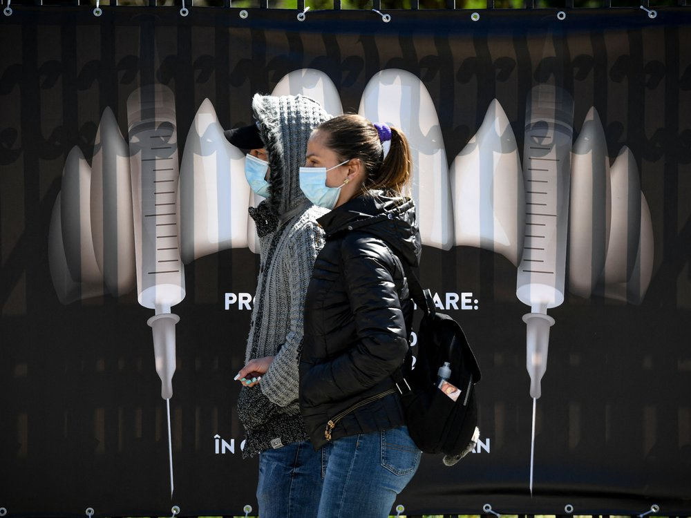 """People wearing protection masks walk by a banner showing syringes as vampire fangs during the vaccination marathon organized at the """"Bran Castle"""" in Bran village on May 8, 2021"""