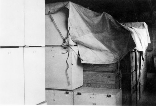 Black and white photo of crates covered with tarp