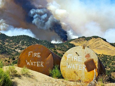 Tanks filled with water await possible use as a fire burns on the crest of a hill in Lebec, California, 2010