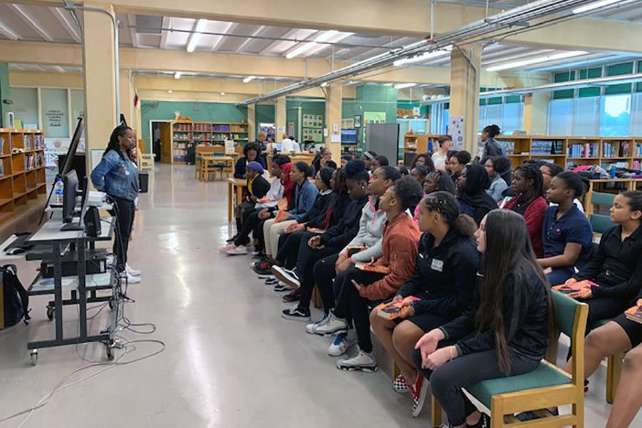 In a school library, a woman makes a presentation to rows of students.