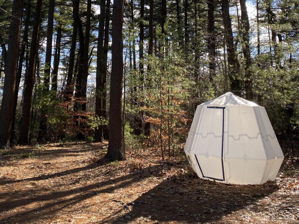 A white octogon-shaped origami tent sits in the woods in New England