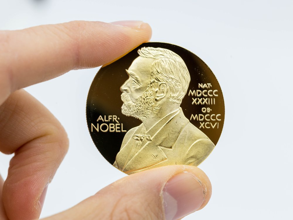 The gold medal that recipients are awarded, featuring the profile of alfred nobel.