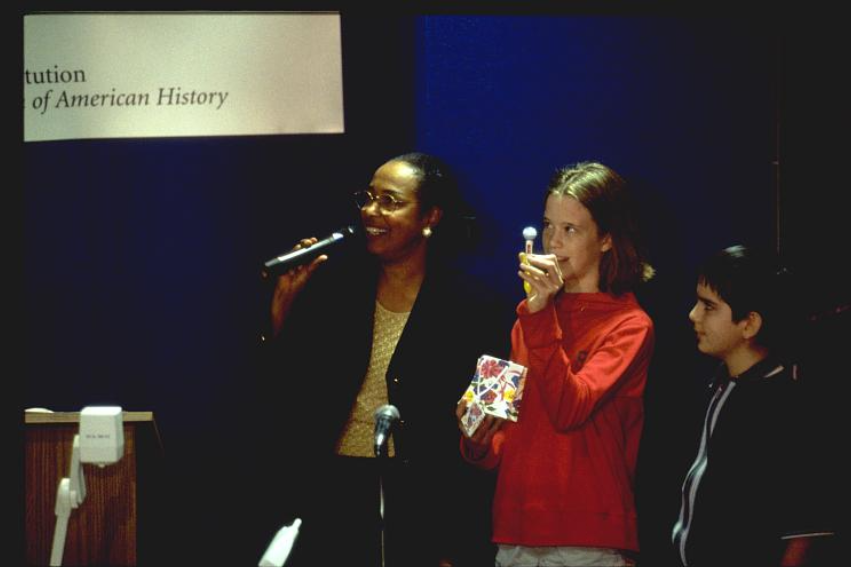 Dr. Bath holds a microphone, speaking from a stage. Two young students stand next to her.