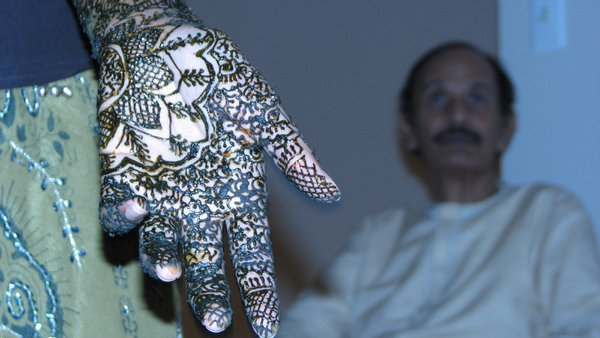 An Indian wedding. The bride and women close to her have their hands decorated with henna paste. thumbnail