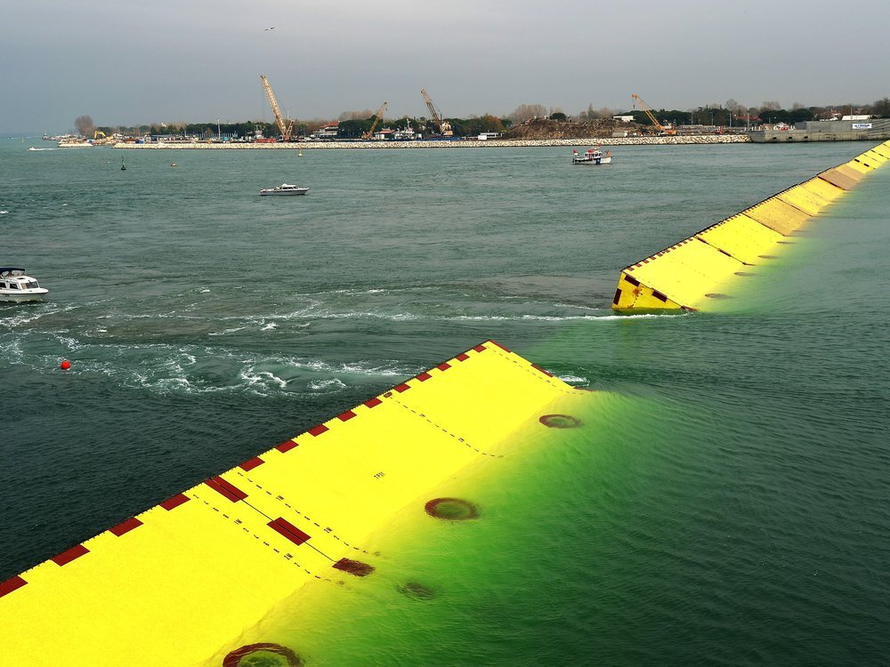 Near the shore, the flood barriers emerge from the water. They are large, bright yellow and triangularly shaped to deflect the water. There are several boats in the water nearby. Lido, a barrier island near Venice, is in the background.