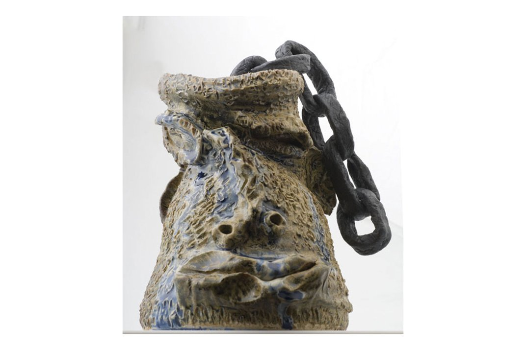 Ceramic sculpture of a human face jug, with a heavy chain coming out of the opening at top. The face looks weathered and collapsing.
