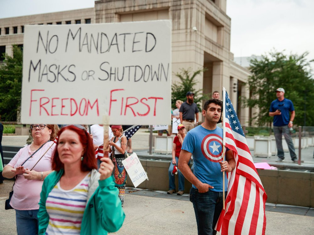 At an anti-mask rally, a protester holds a placard saying No Mandated Masks or Shutdown Freedom First