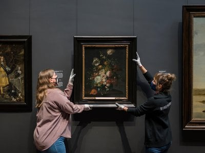 Staff hang a work by Rachel Ruysch in the Amsterdam museum's Gallery of Honour on March 8, 2021.