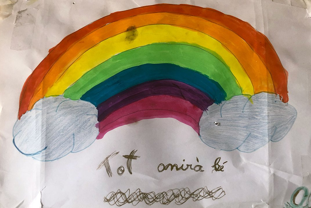 """Child's drawing of a rainbow above the words """"Tot anirà bé""""."""