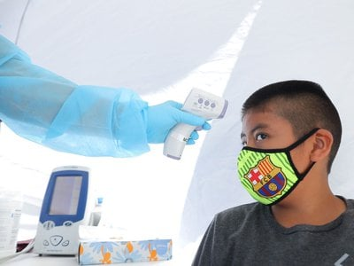 A boy has his temperature checked as he receives a free COVID-19 test in Los Angeles.
