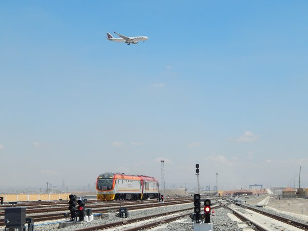 Aeroplane flies over train. thumbnail