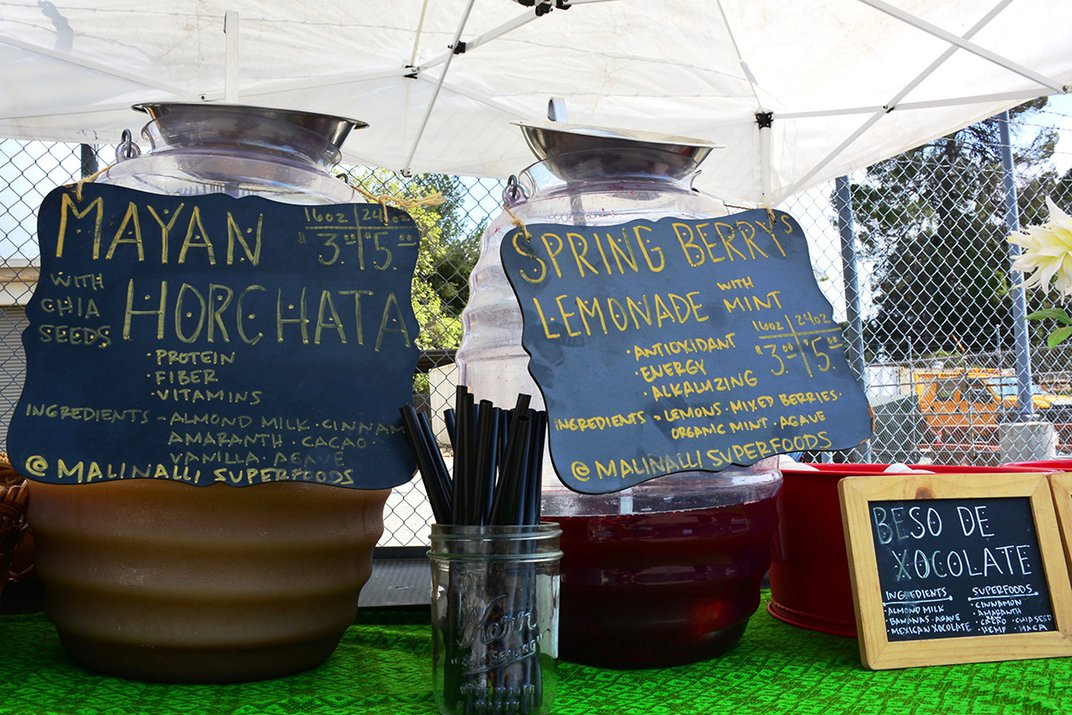 Containers filled with fresh, homemade beverages are places on a table. Hung on the containers are hand-painted signs describing each drink: Mayan Horchata and Spring Berry Lemonade.