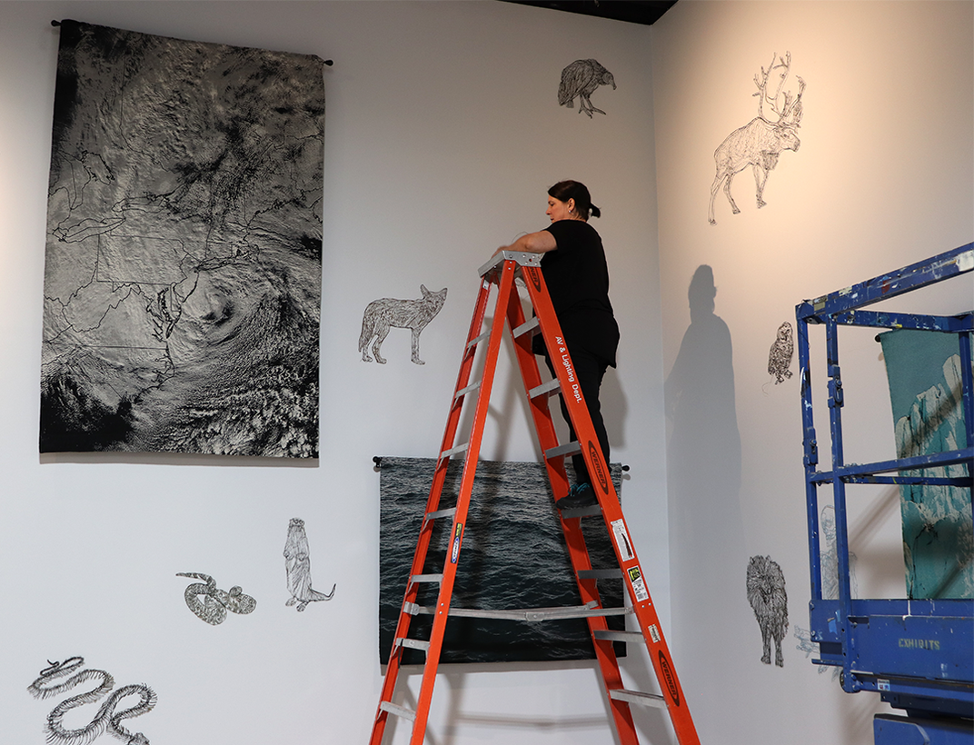 Artist on a ladder hanging art on a white wall