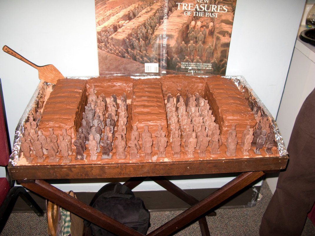 Brown, chocolate cake recreation of a Chinese tomb with brown, solid chocolate recreations of the terracotta warriors inside. The cake is on display on a brown, wood tray table.